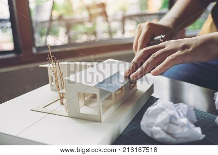 Closeup image of an architect measure scale of a mass model on table in office
