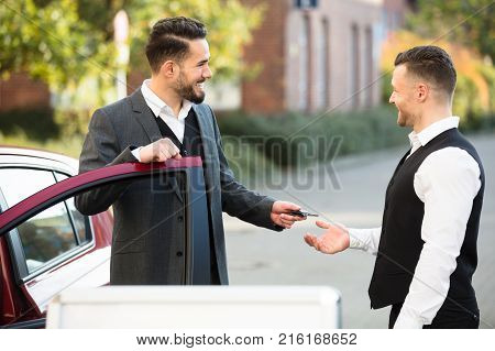Smiling Young Businessman Standing Beside Car Giving Key To Valet