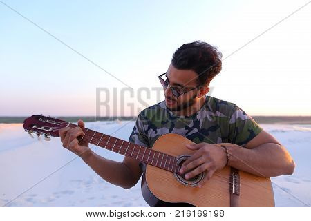 Ambitious budding musician, Muslim guy performs lyrical melody on musical instrument and guitar, and raises skill of professionalism, sitting on sandy hill in middle of wide sandy desert on warm summer evening at sunset. Swarthy man with dark hair and sho