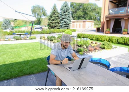 Skilled actuary working with laptop and documents at cafe table. Handsome man dressed in white shirt sitting near green plants on sofa and typing with keyboard.