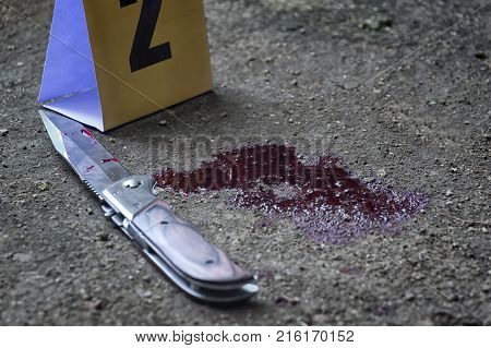 Bloody knife and criminal markers on ground Homicide evidence.Crime scene investigation. (Selective Focus)