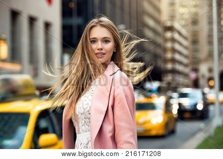 Portrait of the blonde with flyaway hair in the background of New York City street with taxi cabs