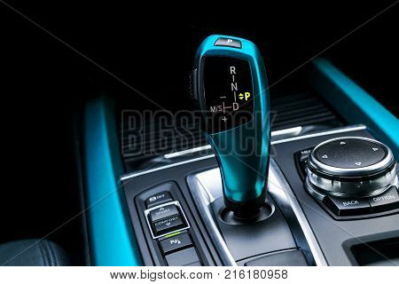 Blue Automatic gear stick (transmission) of a modern car multimedia and navigation control buttons. Car interior details. Transmission shift.