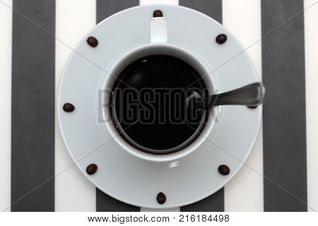 Coffee cup with spoon on saucer and coffee beans against white background forming clock dial. View from above. Coffee as symbol of morning energy and cheerfulness or evening refreshment.