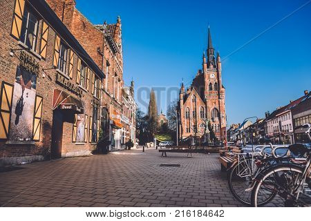 Ghent, Flanders, Belgium - January 2th, 2017. Old brick houses, clock belfry tower of City hall and bikes on street of Sint-Amandsberg district in flemish city Gent.