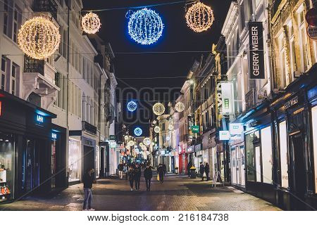 Ghent, Belgium - January 2th, 2017. Medieval flemish city Gent shopping street with modern shops in merchant houses, Christmas illumination, garlands and decorations by Winter festival.