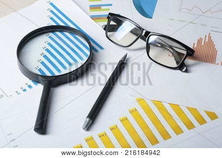 Chart, glasses, pen and magnifying glass on wooden office table.Home savings.budget concept
