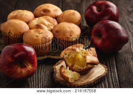 Homemade muffins with apple stuffing on black background..