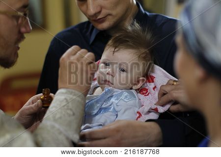 Belarus the city of Gomel St. Nicholas Monastery.June 11 2016.Baptism of the Child.Priestess smears baby's incenseBaby baptismAcceptance of faith.