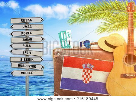 Concept of summer traveling with old suitcase and Croatia with burning sun
