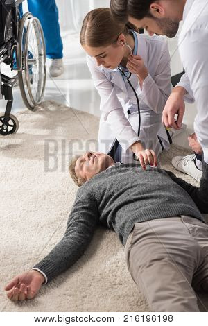 female doctor checking unconscious man palpitation with stethoscope