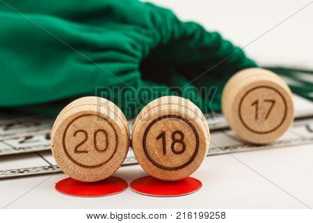 Wooden lotto barrels with numbers of 20 and 18 replace 17 as New Year 2018 is coming concept and game cards for a game in lotto with bag on the background