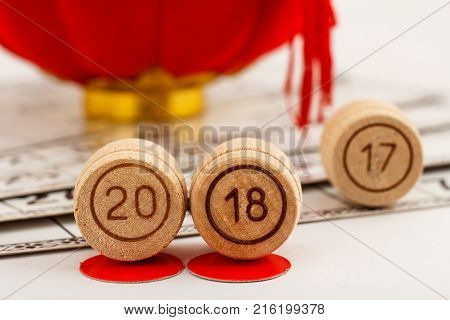 Wooden lotto barrels with numbers of 20 and 18 replace 17 as New Year 2018 is coming concept and game cards for a game in lotto with red decoration on the background