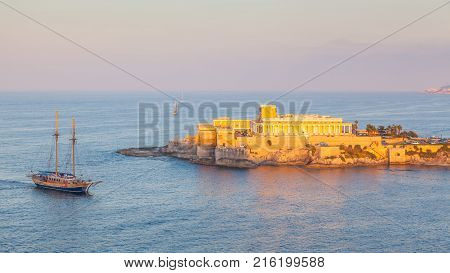 A schooner entering St George's Bay in St Julian in Malta with a casino in the background. Photo taken during the golden hour.