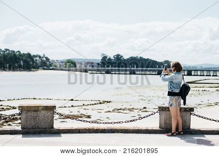 Young female tourist taking a photo on cellphone of the Atlantic ocean, O Grove island, Galicia, Spain. Traveler standing on pier and taking photo of the opposite shore of the bay