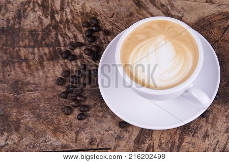 Hot cappuccino or latte art coffee. A cup of coffee on the wooden table. Morning breakfast with coffee.