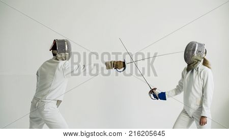 Two fencers man and woman having break after training attack exercises in fencing in studio indoors