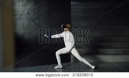 Concentrated young fencer woman practice fencing exercises using VR headset and training simulator competition game indoors