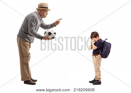 Full length profile shot of a mature man with a deflated football scolding a little boy isolated on white background