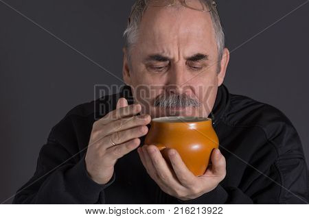 Portrait of mature Caucasian man smelling earthenware pot with food against dark background