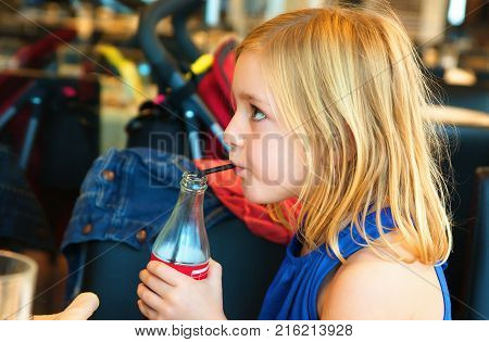 A cute six year old blonde girl in a summer blue dress in the restaurant drinking a soft drink from a bottle with a straw and watches the program on TV turning away from the table