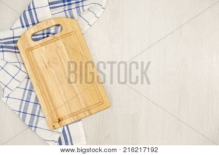 Cutting board over towel on wooden kitchen table. Kitchen blue color kitchen cloth. Food decoration.Textile on a gray background. mockup, Top view. flat lay. copy space for text