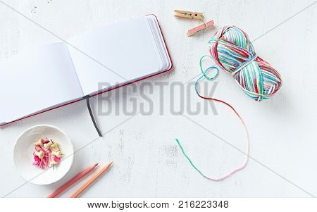 Multicolored cotton yarn, notebook, pink pencils and paper clips on white background