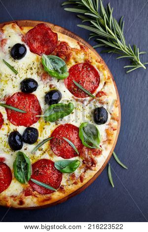 Pizza with salami, black olives and herbs (top view)