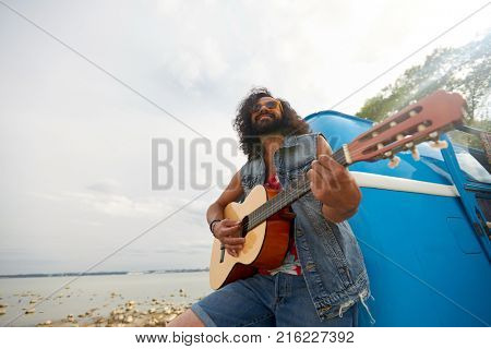 summer holidays, road trip, travel and people concept - happy smiling hippie man playing guitar near minivan car outdoors