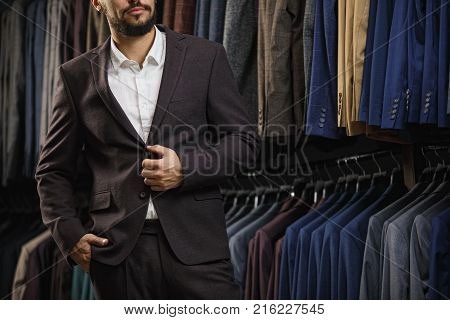 sale, shopping, fashion, style and people concept - elegant young man in suit choosing suit in mall or clothing store