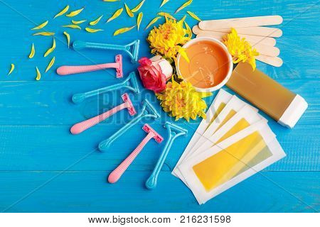 Set for depilation with strips, razors multi-colored, wax, chopsticks and cassette with wax on a blue wooden background. Top view of a closeup