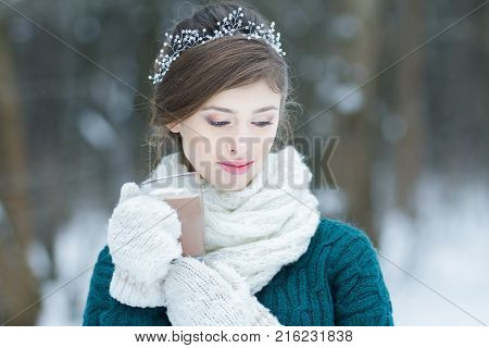 Daydreaming woman holding hot cocoa glass cup with melting marshmallows