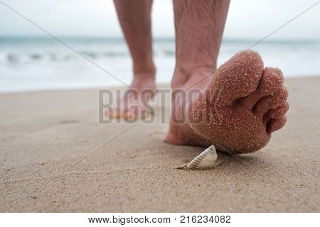 Man goes on the beach and is going to stand up on broken sharp shell. Go for a walk on seashore