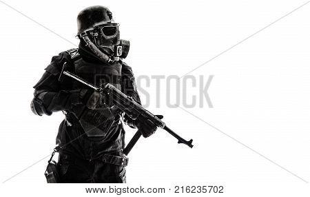 Futuristic nazi soldier sentinel gas mask and steel helmet with schmeisser handgun isolated on white studio shot standing to attention profile