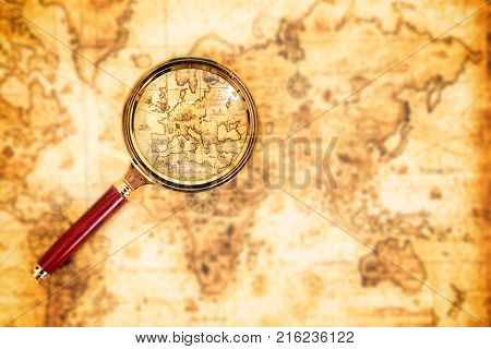 Old map with an magnifying glass exploring it. Vintage travel background
