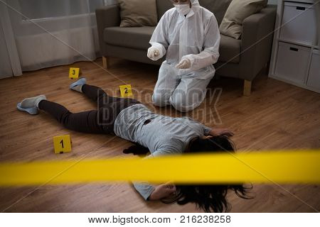 investigation and forensic examination concept - criminalist collecting evidence of murder of woman at crime scene fenced by police tape (staged photo)