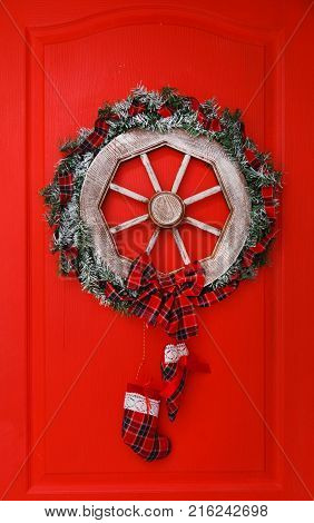 Christmas wreath, cones and evergreen boughs on a red door.