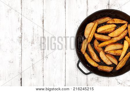 Potato wedges in a cast iron pan on light wooden background top view