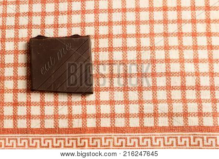 piece of chocolate over table with written eat me