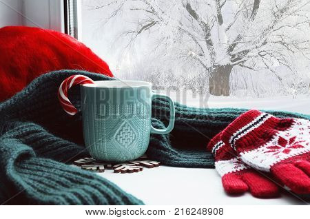 Winter background - cup with candy cane scarf and gloves on windowsill and winter scene outdoors. Winter still life, concept of spending winter time at cozy home with winter weather outdoors. Festive winter composition, winter card