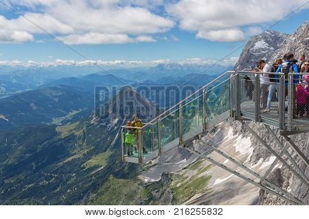DACHSTEIN MOUNTAINS, AUSTRIA - JULY 17, 2017: Dachstein Mountain in Austria with hikers taking pictures at a view platform of a steel skywalk rope bridge