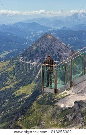 DACHSTEIN MOUNTAINS, AUSTRIA - JULY 17, 2017: Young man at view platform of skywalk rope bridge Dachstein Mountains in Austria