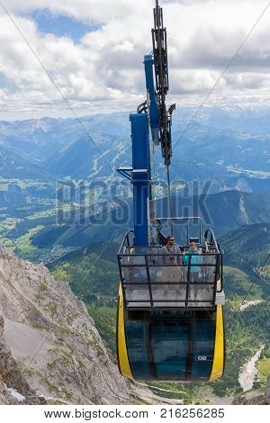 DACHSTEIN MOUNTAINS, AUSTRIA - JULY 17, 2017: Aerial view cable car approaching the Dachstein glacier mountain station in Austria. Some people are standing at the balcony at the roof of the cable car