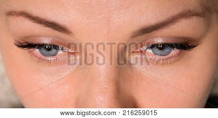 Close-up face of beautiful young woman with beautiful blue eyes and big pretty eyelashes and eyebrows. Macro of human eye - open.