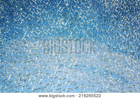 Blue sky behind broken glass surface. Abstract background. Aged photo. Hardened glass surface cracked on a small pieces. Cracked Texture.