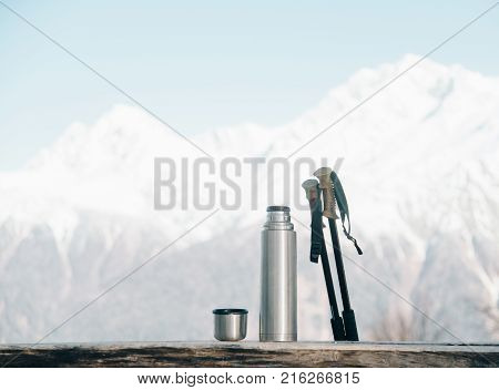 Thermos and trekking poles on wooden table on background of snowy mountains in winter.