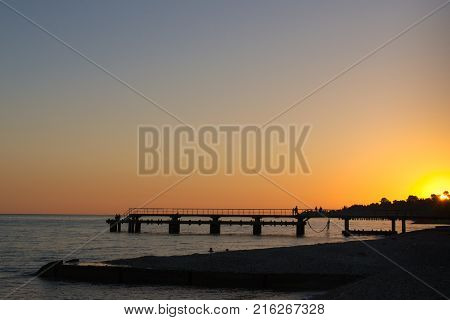 Sea pier at sunset. Silhouettes of people on a sea pier during sunset