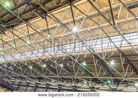 Metal trusses covering an industrial long-span building with an antiaircraft lantern of natural light