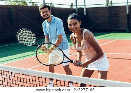 This tennis game is amazing. Beautiful young couple playing tennis on the tennis court and looking at camera with smile.