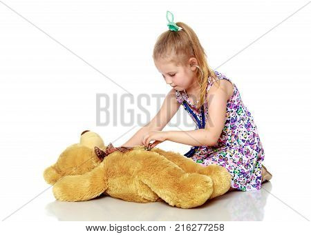 Little girl is playing doctor. She listens through a phonendoscope of a teddy bear. The concept of family happiness, people, children, childhood, games.